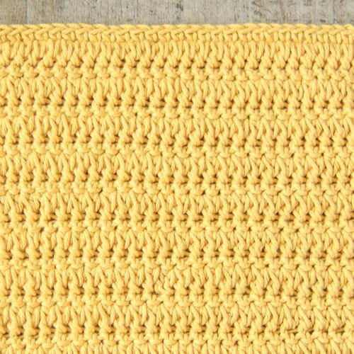 Des rangées de points de grappe fourchus alternés avec des points de crochet simples travaillés dans le dos uniquement.